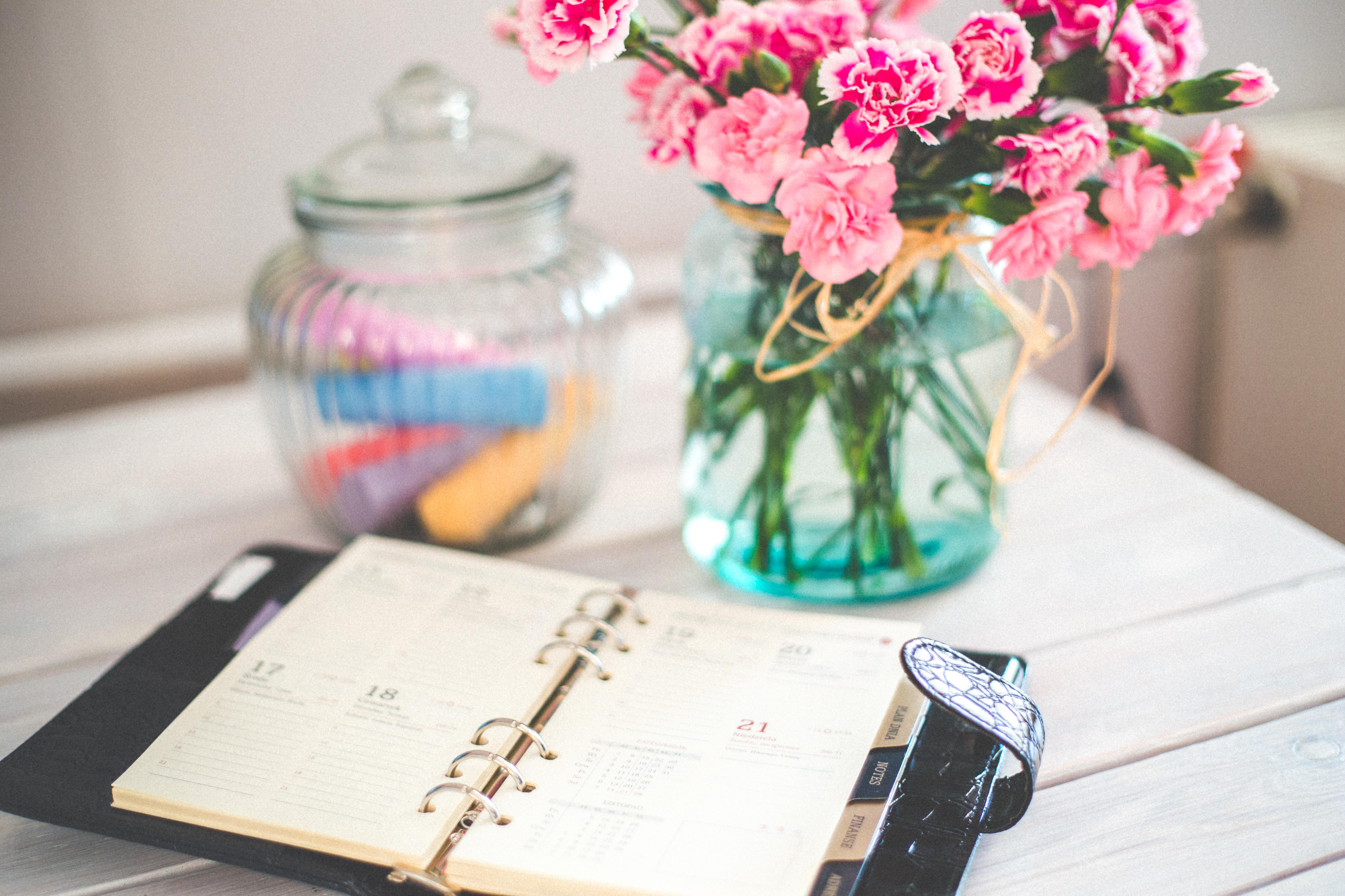 Blumen und ein Kalender liegen auf dem Tisch