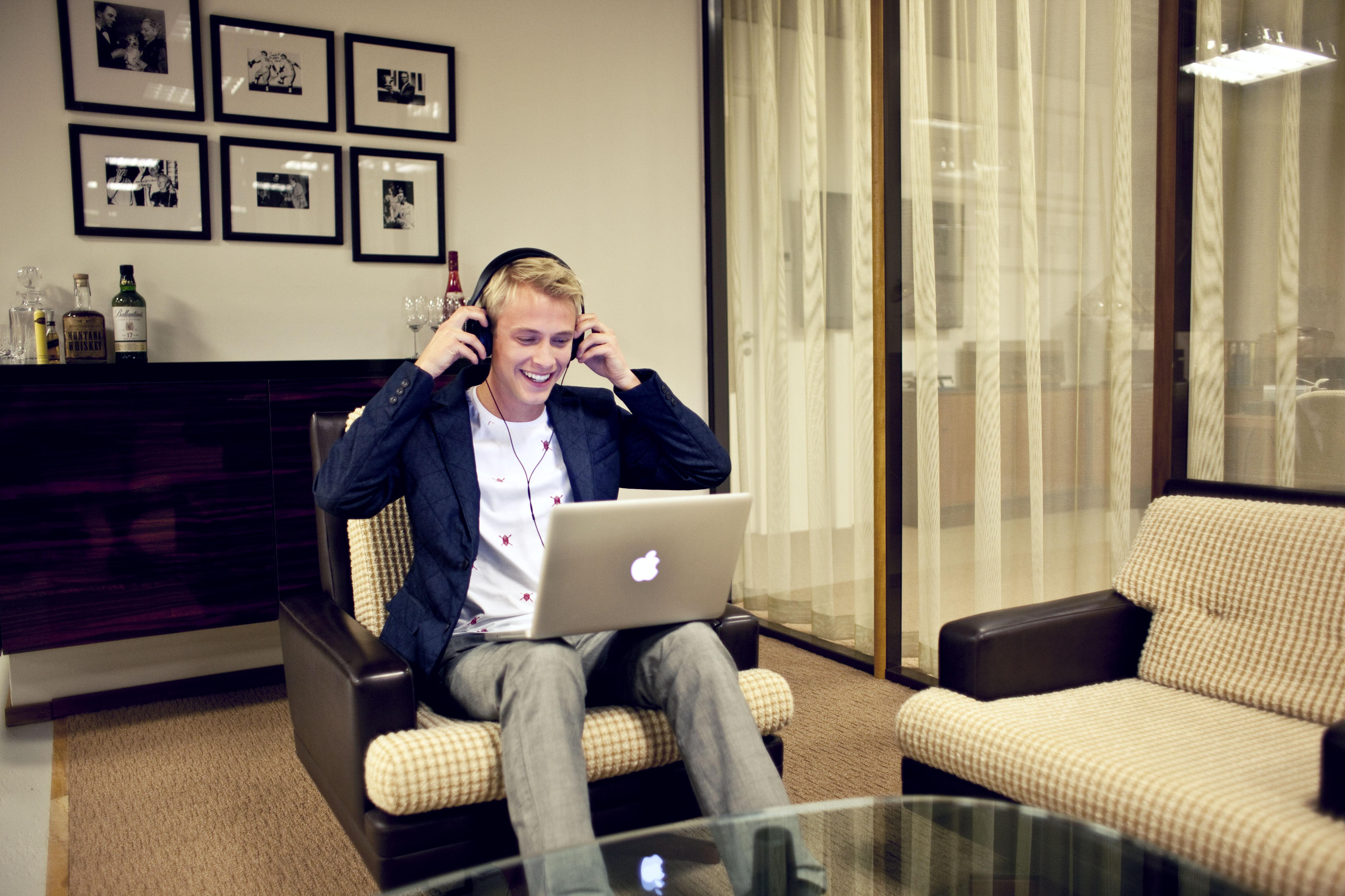 Junge sitzt mit Kopfhörer auf einem Sessel