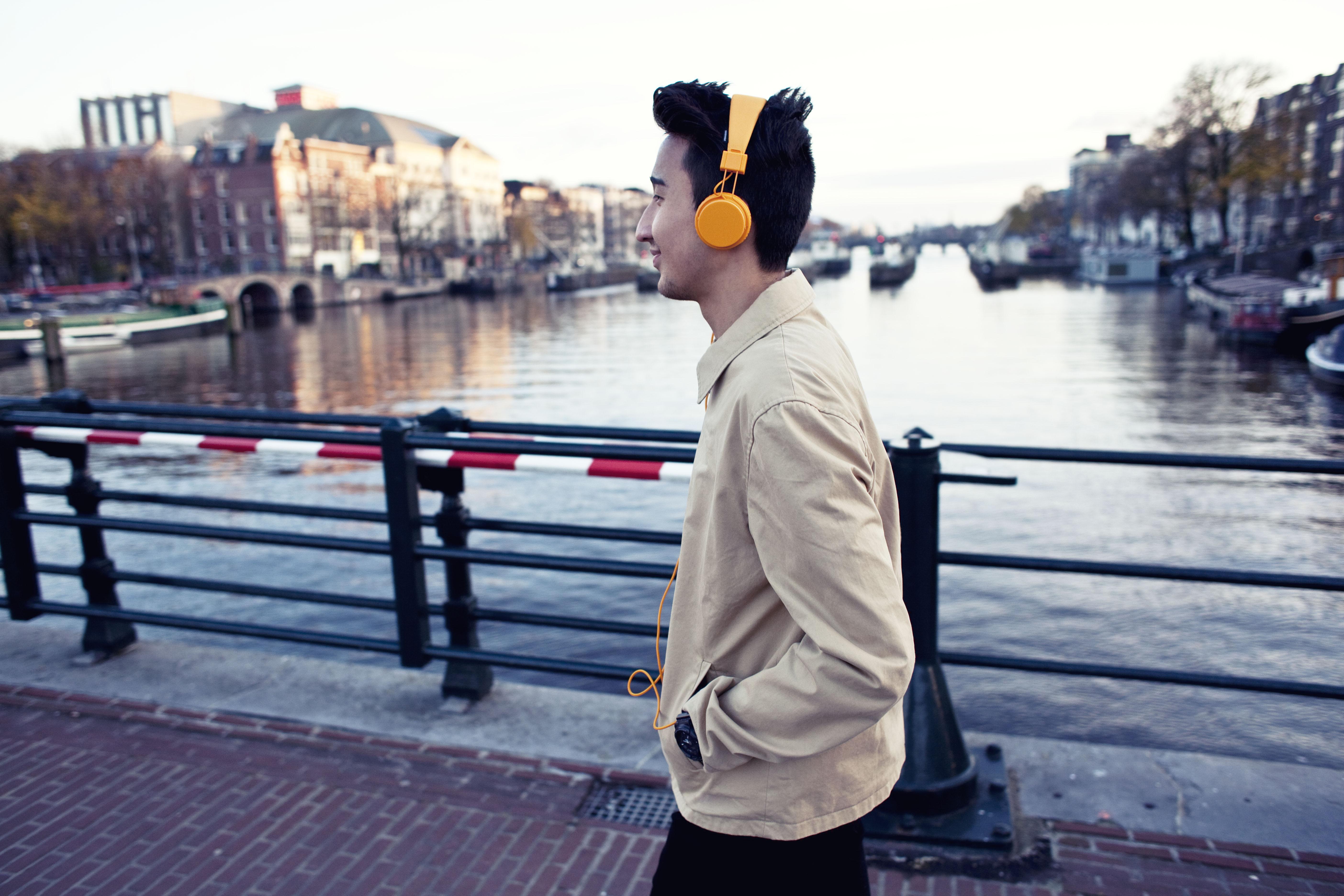 Junge läuft mit Kopfhörern über eine Brücke