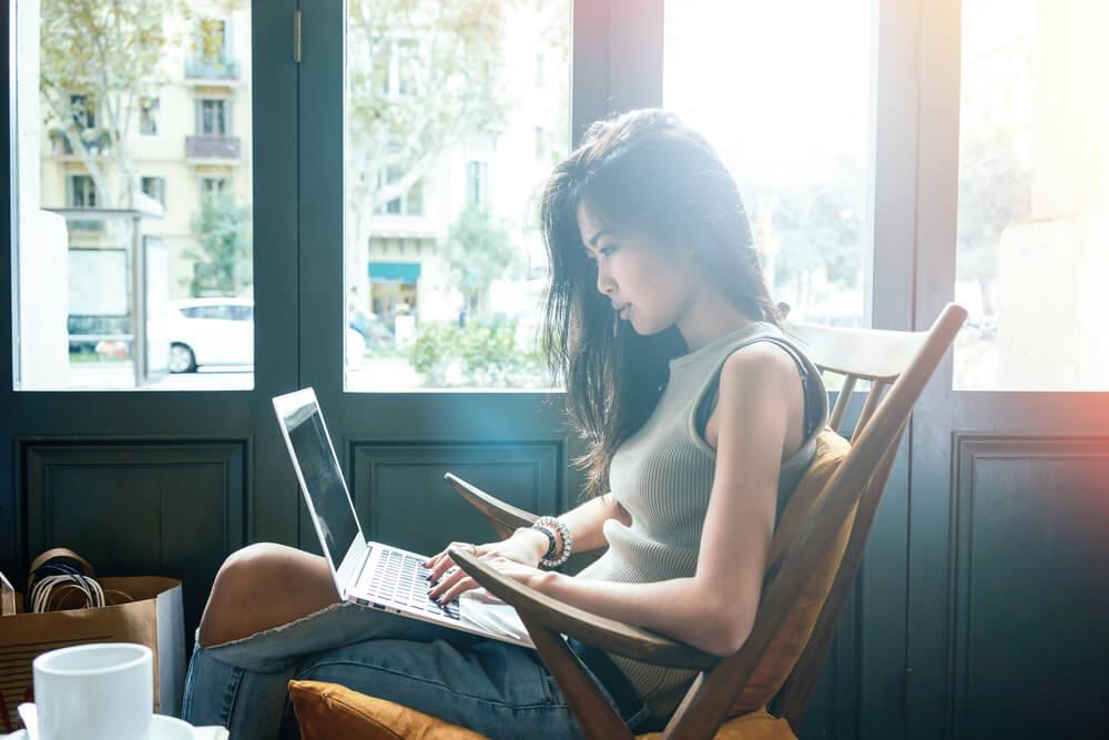 Chica trabajando con su ordenador en cafetería