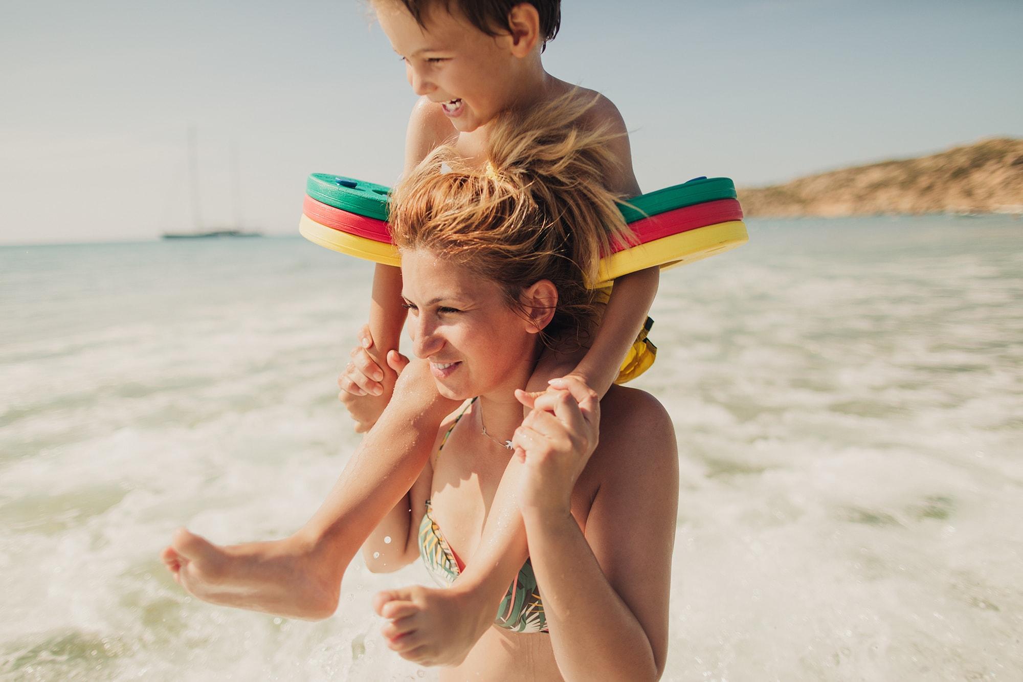 Ein Kind sitzt auf den Schultern einer Frau