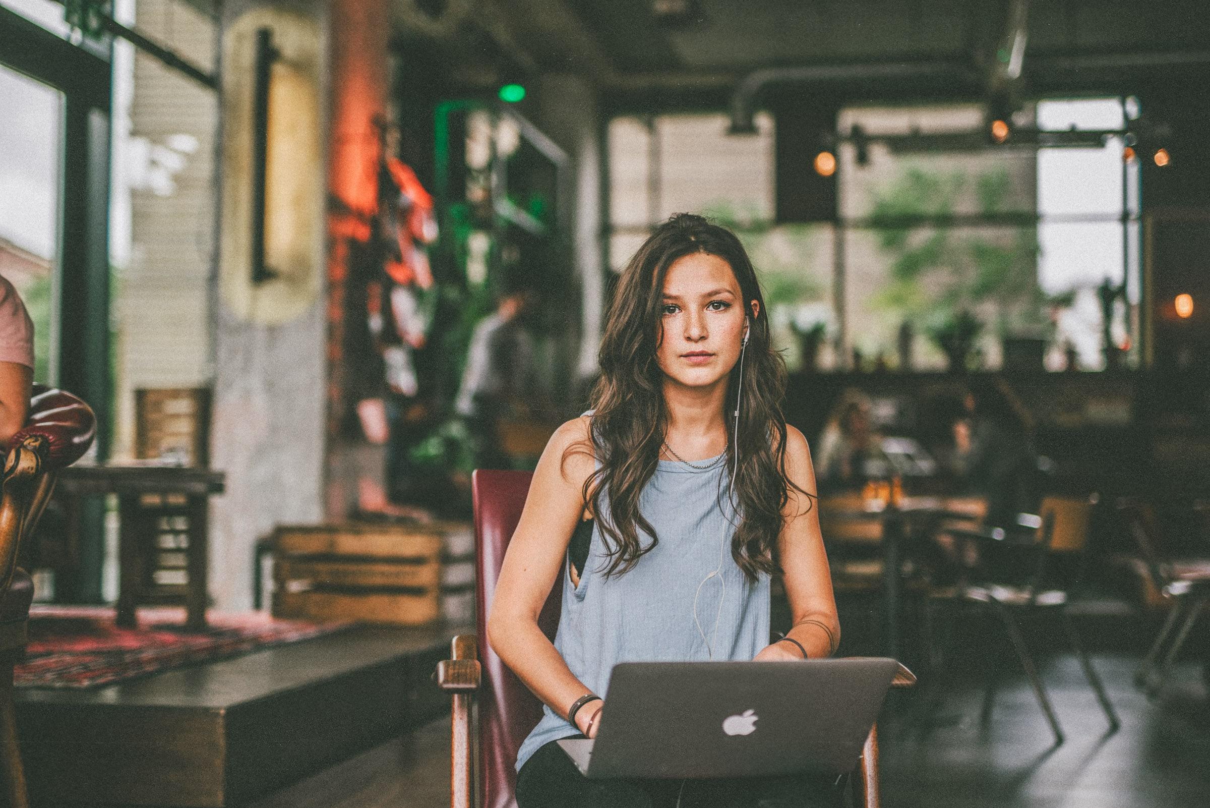 Mädchen sitzt auf einem Stuhl mit einem Laptop