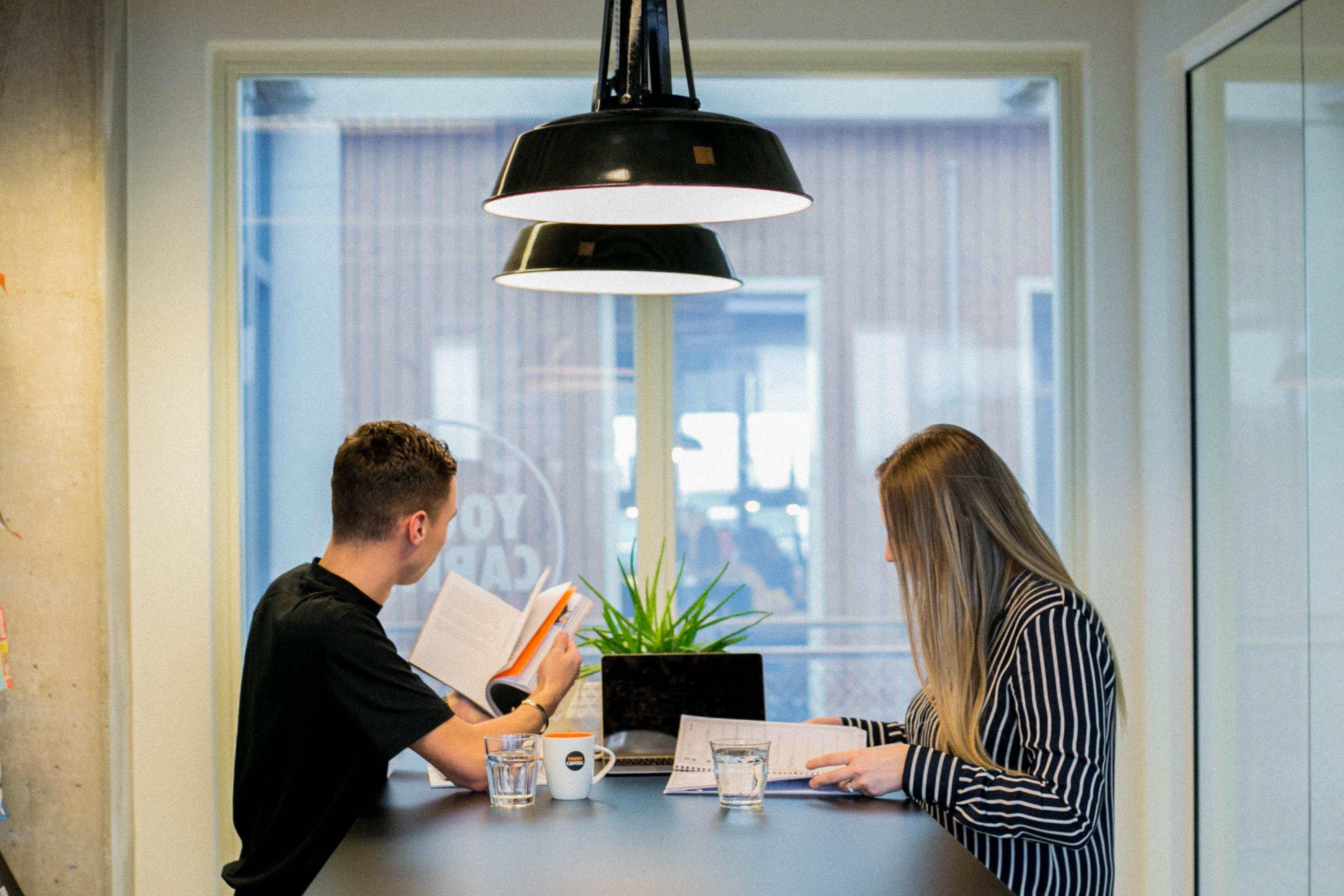 Zwei Personen sitzen am Tisch