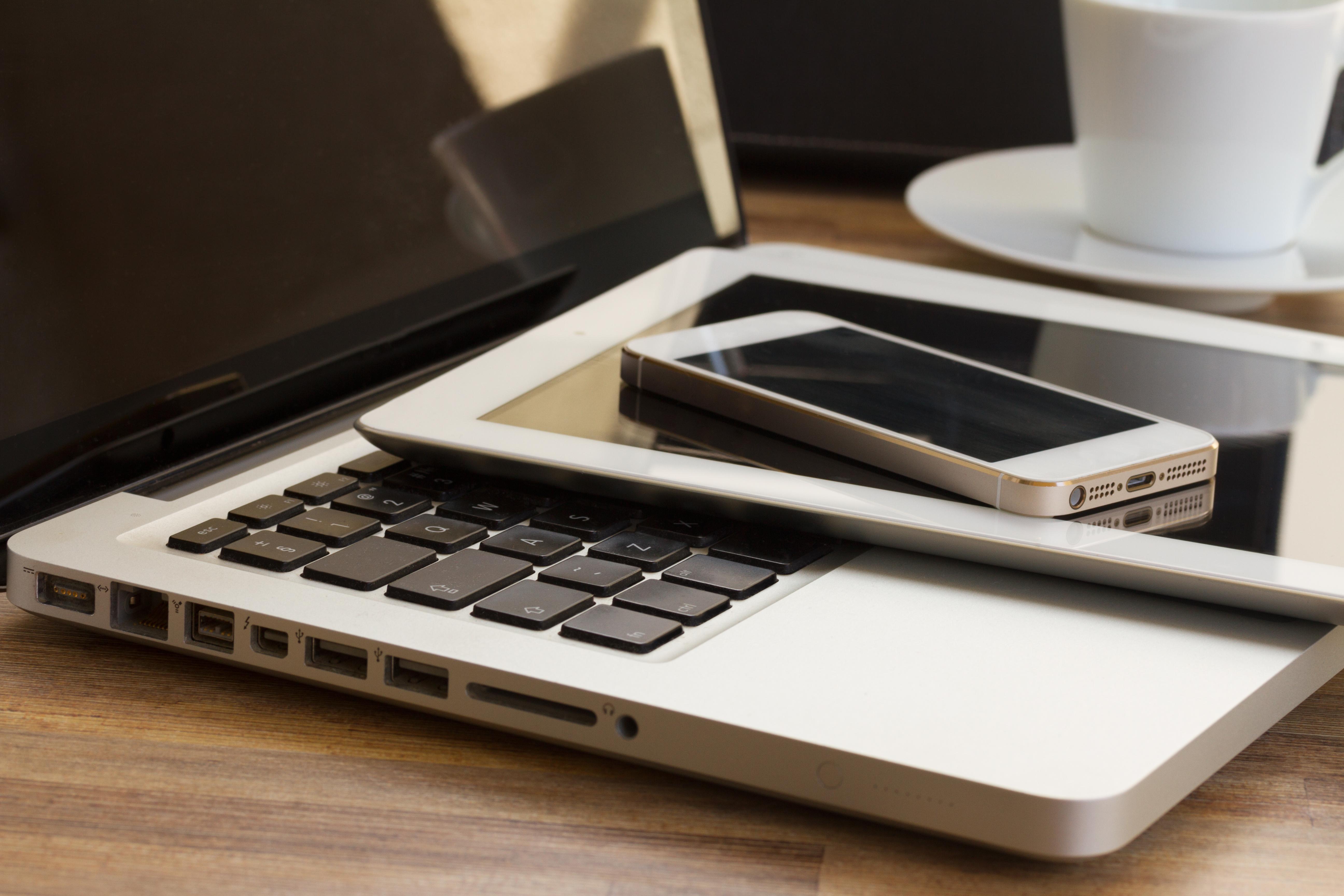 Laptop, Tablet und Handy liegen auf dem Tisch