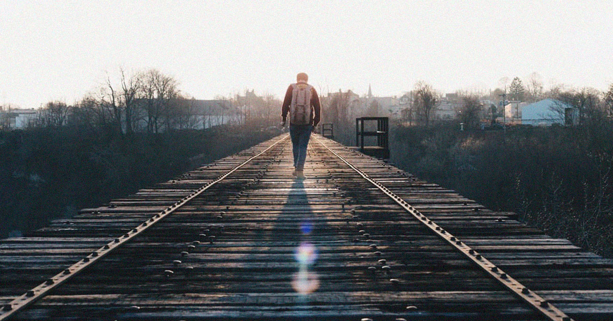 Man walking on railway in backlight