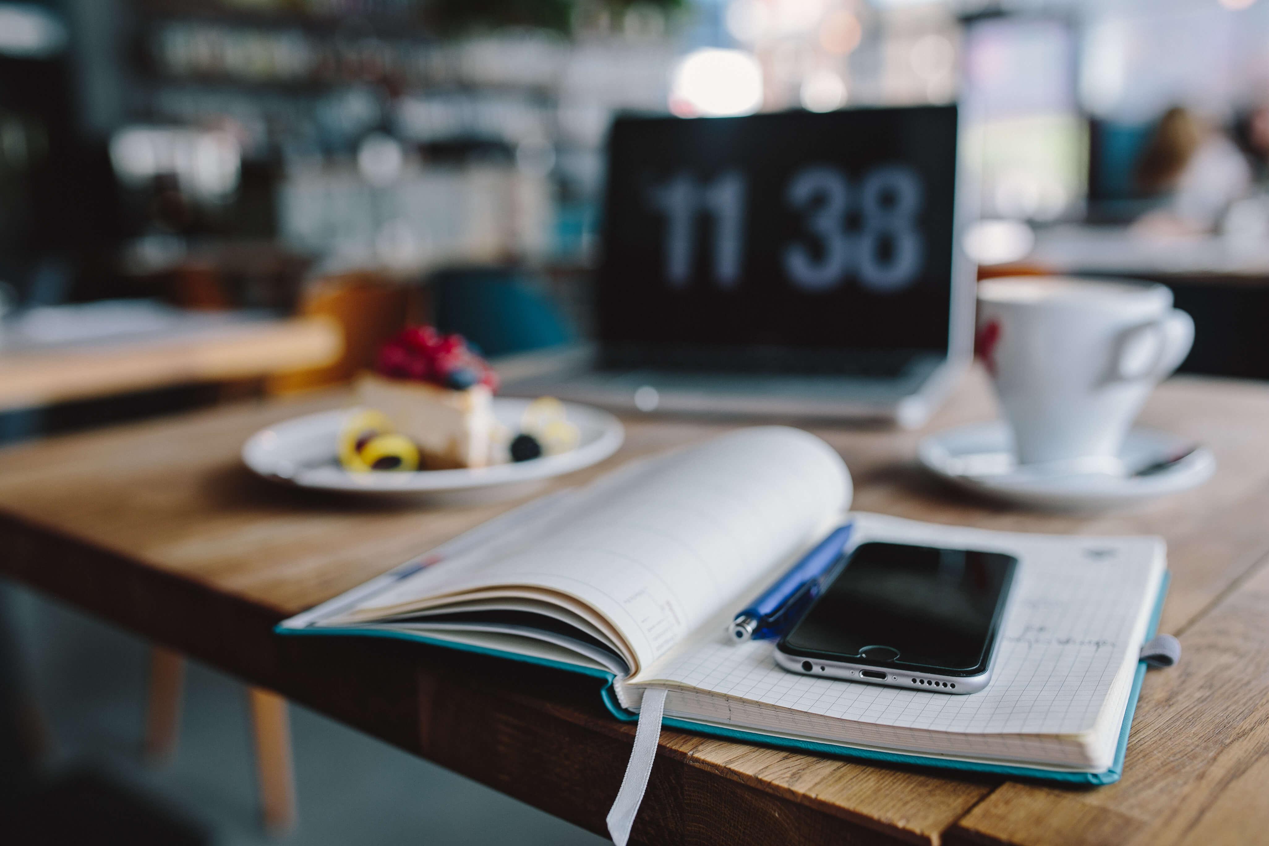 agenda y móvil sobre una mesa de cafeteria