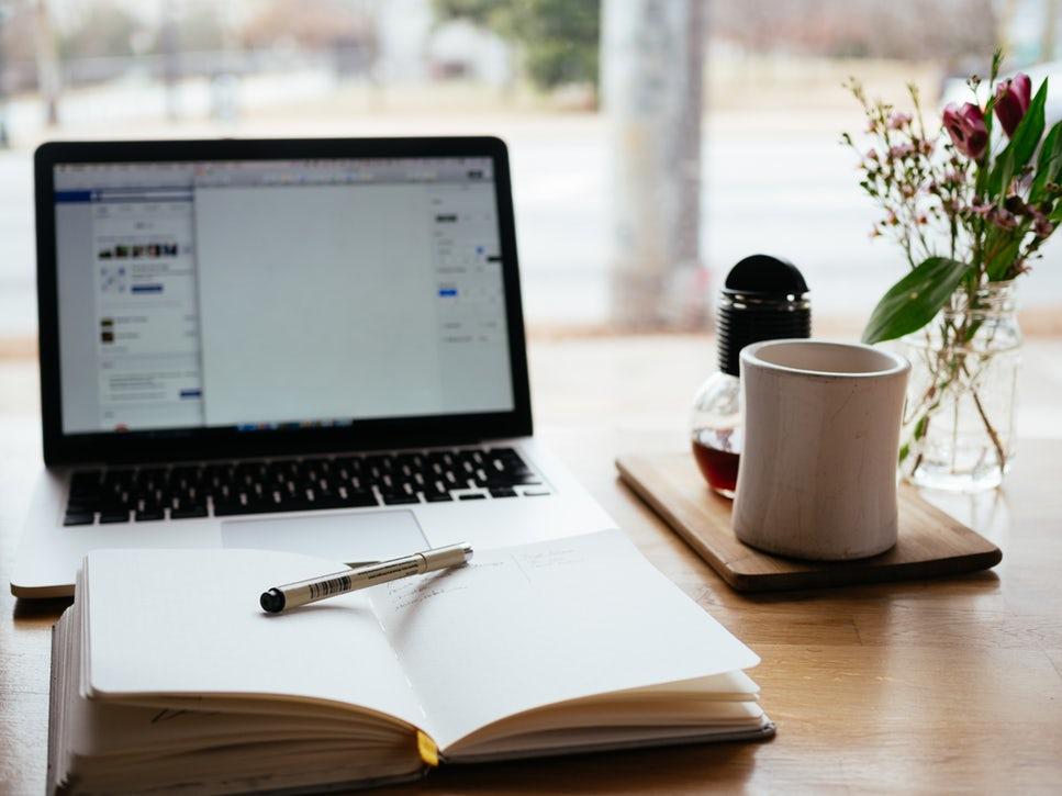 Laptop mit Notizbuch und Tasse