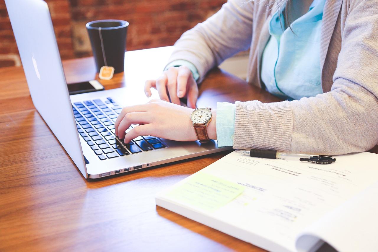 Mann am Schreiben an seinem Laptop mit Tee und Smartphone