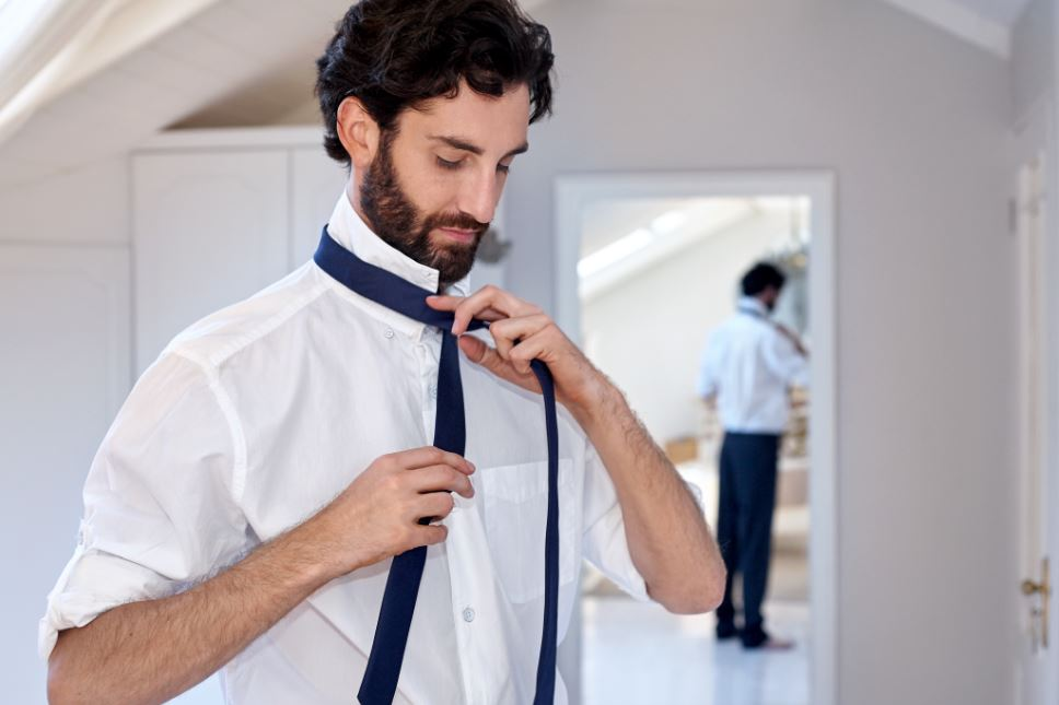 Man trying to tie his tie