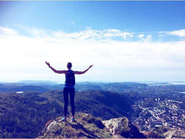 Lycklig tjej på fjälltopp i Norge