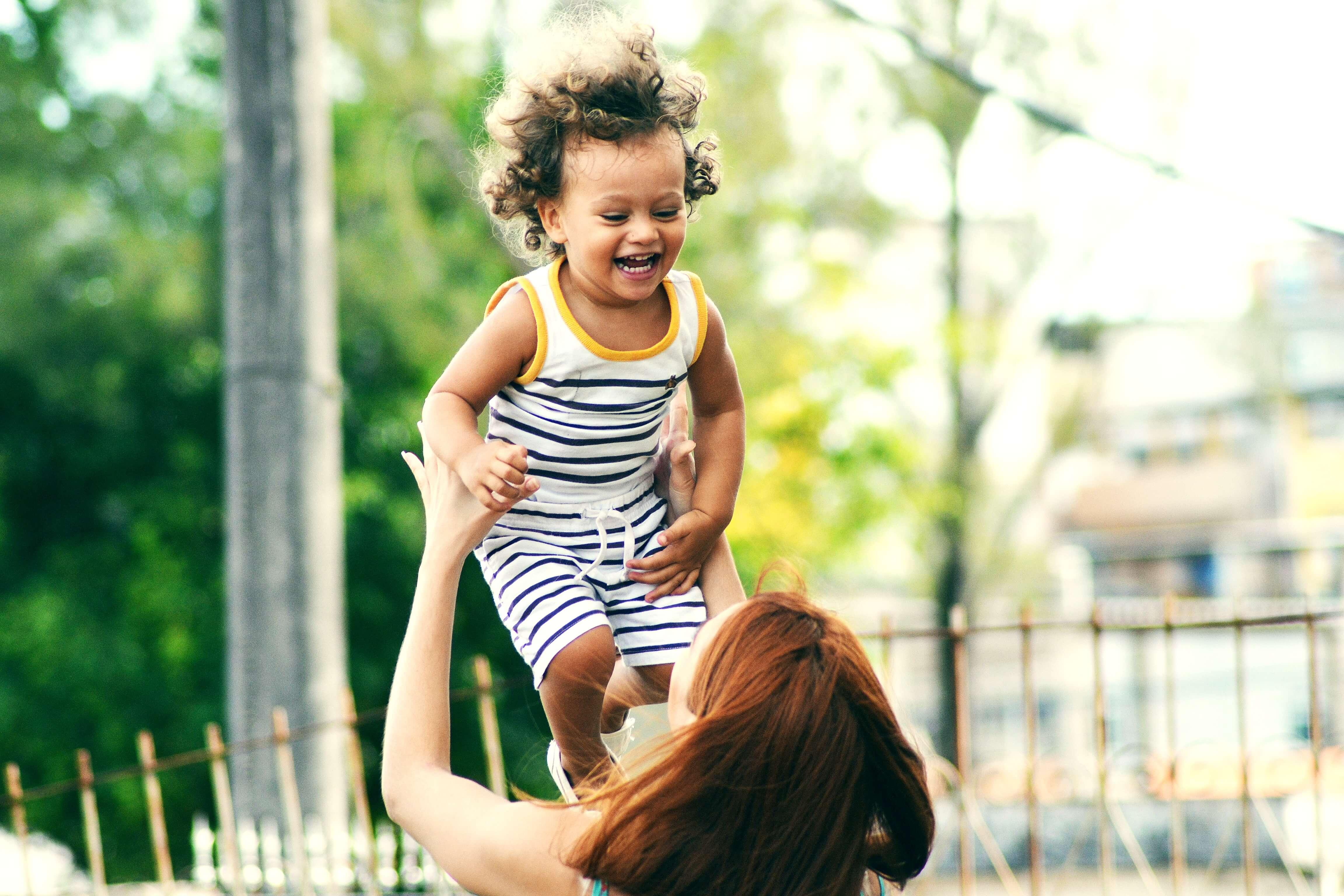 mujer lanzando a niño pequeño al aire
