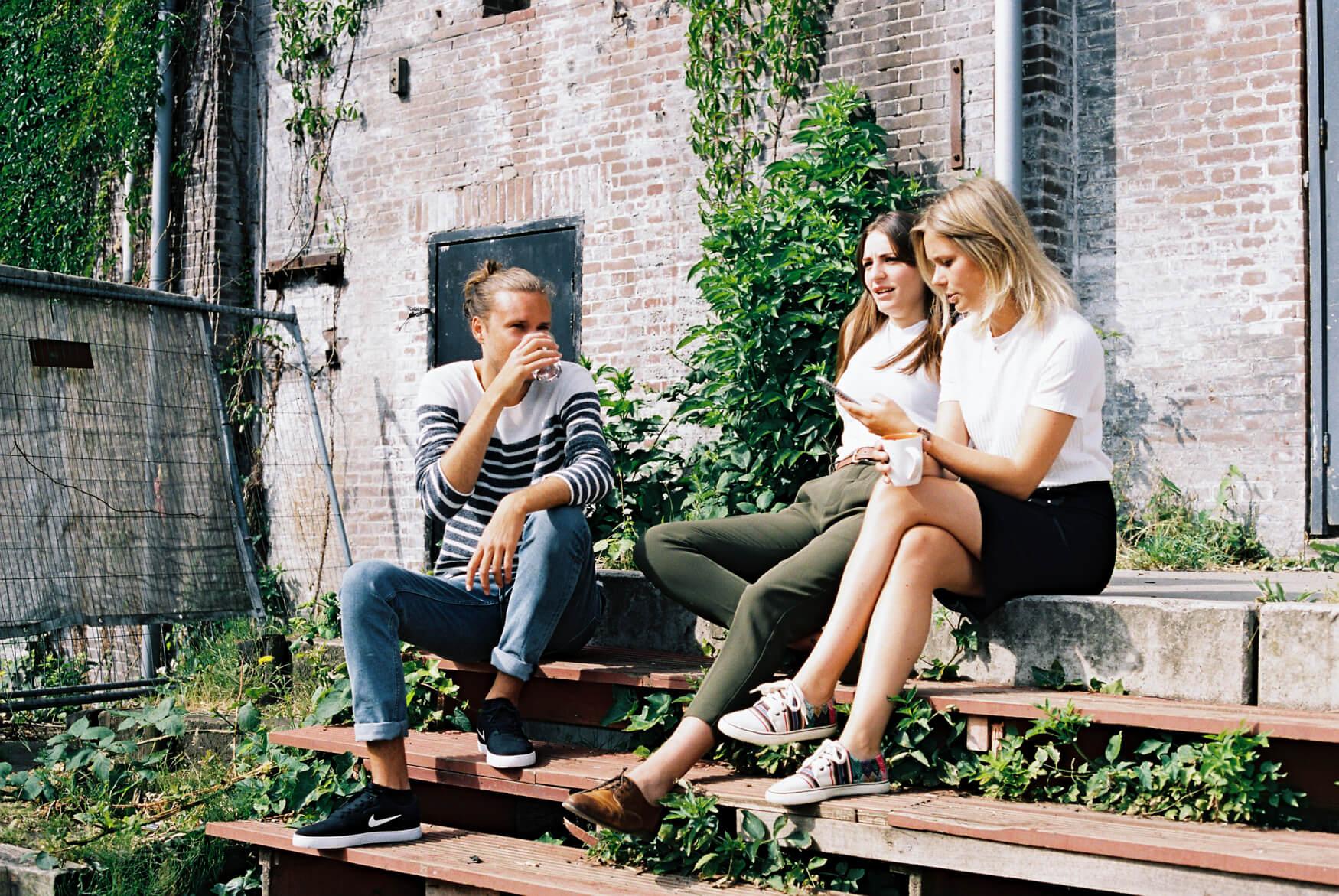 3 jóvenes sentados en las escaleras tomando café